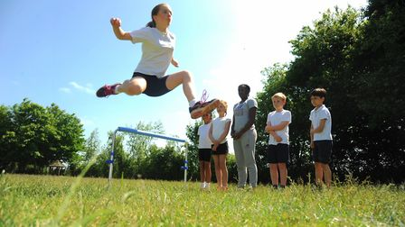 Libby takes to the air in hurdle practice watched by Abigail, Emily, Commonwealth Athlete Serita Sol
