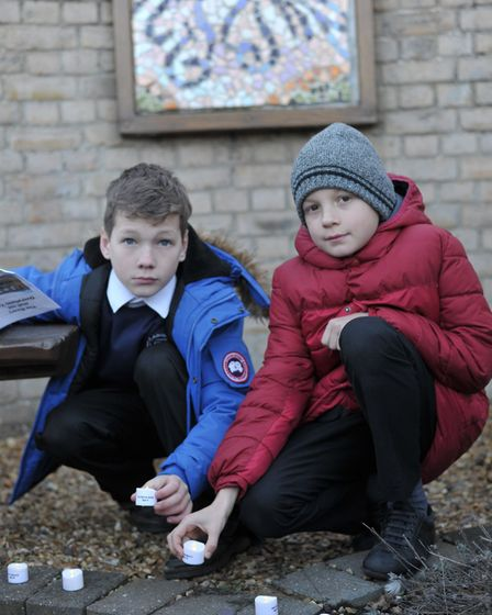 Children from Langer Primary Academy place candles as the names of the dead are called. Picture: