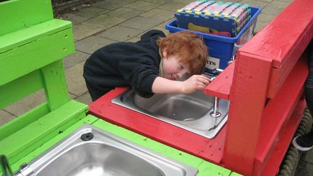 One of the children at HOPS enjoying the new sensory busy board. Picture: HOPS