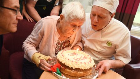 Evelyn Dixon blows out the candles on her 103rd birthday cake. Picture: GREGG BROWN