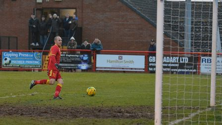A delighted Adam Mills taps the ball home for Needham's third goal. Photo: BEN POOLEY.
