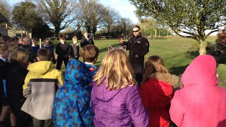 Pc Nick Lofthouse from Suffolk Constabulary's dog section gives a talk on his work to pupils at the