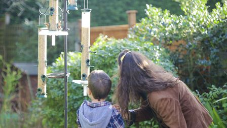 Undated Handout Photo of mother and son putting out feeders. See PA Feature GARDENING Bird. Picture