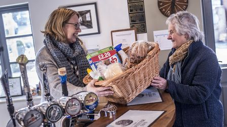 Judi Newman behind the bar at the Oyster Inn serving Audrey Boast, of Butley WI, with goods from the