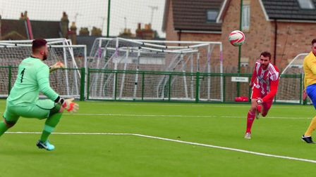 Felixstowe's Joe Francis guides his header past Newmarket keeper Alex Archer on Saturday. Picture: S