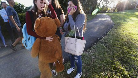 Students wait to be picked up after a shooting at Marjory Stoneman Douglas High School in Parkland,
