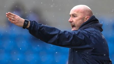 Colchester United boss John McGreal gives out instructions as the snow comes down at the Community S