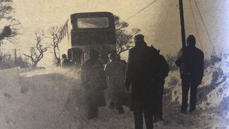 Passengers watch as attempts are made to free a bus from drifts at Hacheston. It was on its way from