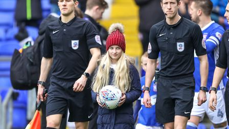 Ellie Kirk, the Young Community Champion, leads the teams out onto the pitch ahead of the Ipswich To
