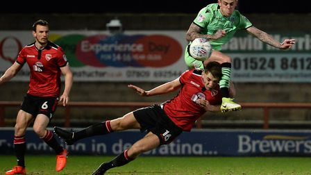 Sammie Szmodics goes in high with Morecambe defender Sam Lavelle. Picture: RICHARD BLAXALL