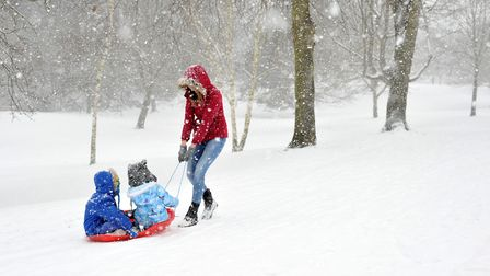 Rebecca Bantick with her children Joey and Millie in the snow at Christchurch Park. Picture: SARAH L