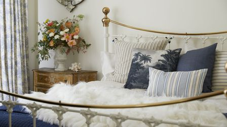Daisy Lowe's bedroom with bed layered in sheepskin throws and accessorised with cushions. An 18th ce