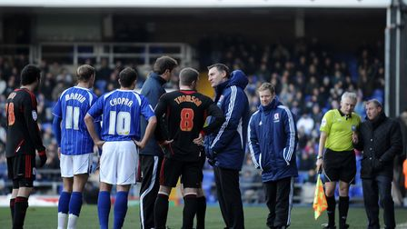 Players and staff from Ipswich Town and Middlesbrough talk to the officials about frozen conditions