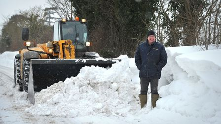 Dan Kiddy next to some of the snow drifts near Wickham Market. Picture: SARAH LUCY BROWN