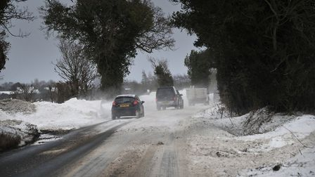 Cars drive through a snow drift on the road out of Woolverstone. Picture: SARAH LUCY BROWN