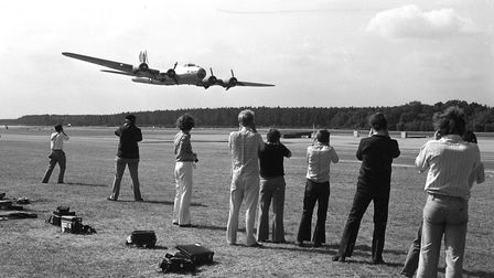 Enthusiasts watch as a B-17 flies low