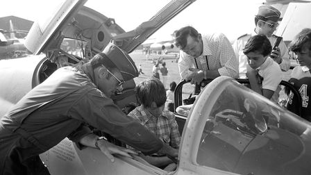 A young guest is shown the inside of a cockpit on one of the many aircraft on display