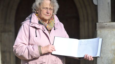 Church Warden Jenny Cox with the visitor book that has had a page torn out of it. Picture: SARAH LU