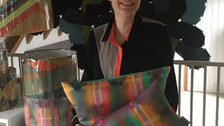 Sarah Parris at Mellis-based Colour and Form with some of the cushions to be displayed at the GREAT