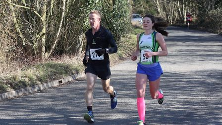 Jessica Prior, right, on her way to victory in the Tarpley 10 on Sunday. Ely's James Mann,, left, is