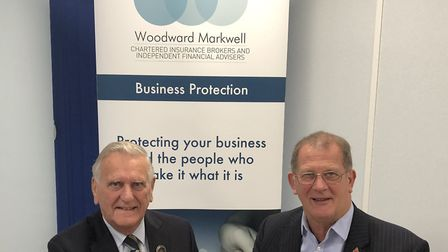 Suffolk Golf Union president Colin Firmin (left) and Andrew Johnson of Woodward Markwell seal a thre