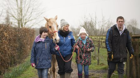 Celia Newman, Depden Care Farm staff member, leads Athena the horse, with farm helpers Laura, Jade a