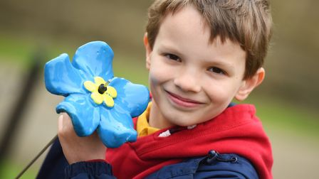 William Stokes with one of the ceramic flowers . Picture: GREGG BROWN