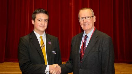 Current head boy Ethan Perry (left) shakes hands with the school's first ever head boy Barrymoore Co