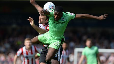 Olamide Shodipo gets pushed off the ball at Lincoln City, during a keenly contested League Two duel
