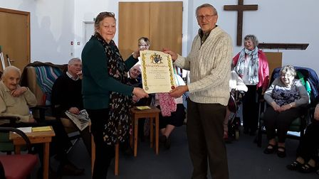 Carol Bull, ward councillor for Barningham, presents Eddie Sier with his scroll of honour. Picture: