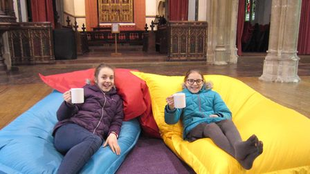 Sisters Rosemay Gray, 12, and April Gray, 10, enjoy a drink and the bean bags at the Bridge Project