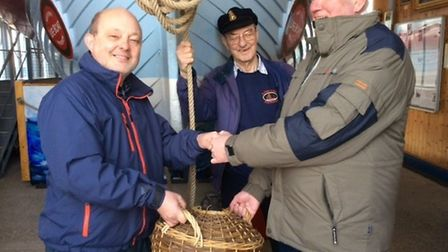 Dave Cragie presents a water breaker to museum curator Frank Upcraft, while Captain John Cragie look