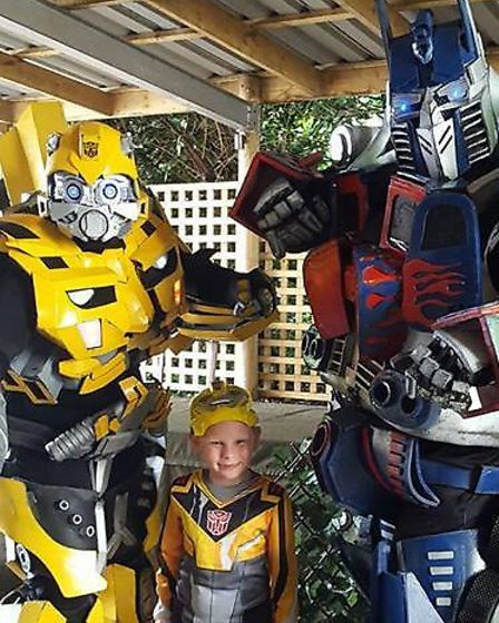 Bumble Bee and Optimus Prime posing with a Transformers fan. Picture: LEE HALL