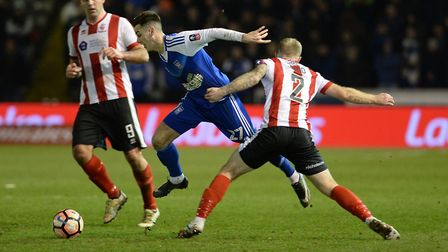 Tom Lawrence is hauled down by Lincoln's Bradley Wood in Town's FA Cup replay defeat at Sincil Bank.