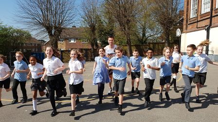 Pupils at St Helen's Primary School help Mr Jarvis with his last training run. Picture: RICHARD LANG