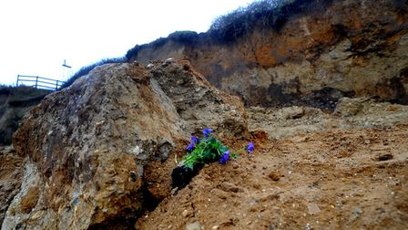 Flowers were left at the scene of the cliff collapse where Brendan Lavery lost his life. Picture: AN