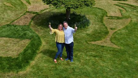 Sue Richards, 51 and 58-year-old Barry Maddox with their new lawn design of a giant champagne bottle