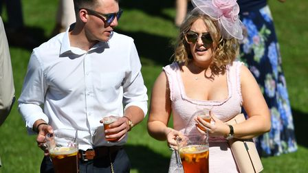 Racegoers carry drinks during day one of the QIPCO Guineas Festival at Newmarket Racecourse. Picture