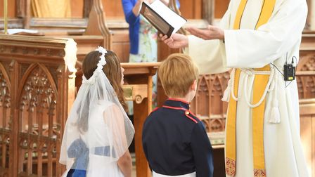 Year 5 class and reception class from Long Melford Church of England Primary School staging a weddin