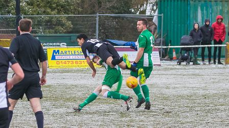 Woodbridge's ex-Ipswich Town star Carlos Edwards is upended by a Whitton tackle. The two teams meet