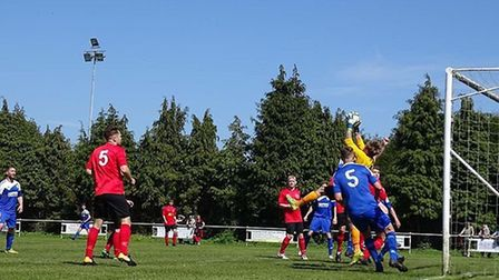 Leiston St Margarets' keeper Andy Perkins claims under pressure from AFC Hoxne attackers. Picture: B
