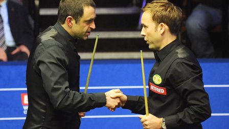 Ali Carter (right) shakes hands with Ronnie O' Sullivan after beating him 13-9 during day eight of t
