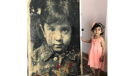 Mina at home after signing her portrait, created by Gillian Allard, with her hand and foot prints. T