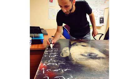 Hamam, from Syria adds his own very personal words to Gillian Allard's artwork at Suffolk Refugee Su