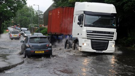 Vehicles head through flood waters in Holywells Road, Ipswich, after heavy rain - weathermen say the