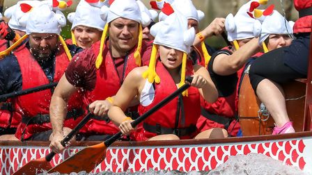 A lady in the Gilmour Piper Dragon Boat having trouble with her fancy dress hat during one of the ra