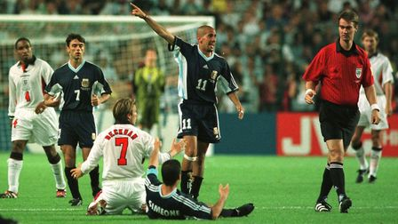 England's David Beckham protests his innocence before being shown the red card by referee Kim Milton