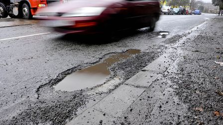 Car driving around a pothole. Picture: PA