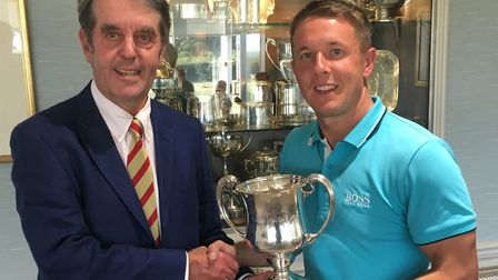 Danny Western of Gorleston receives the Seaton Robson Trophy from Aldeburgh vice-captain Antony Dear