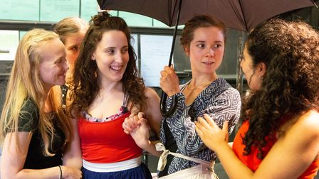 The villagers gather under an umbrella during rehearsals for Polstead, Eastern Angles summer tour wh